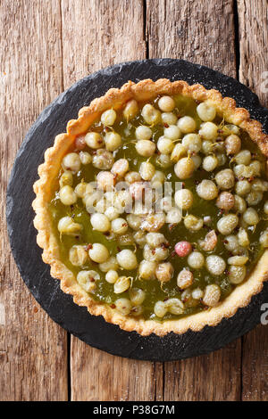 Homemade pie with summer gooseberries and  jam closeup in a board. vertical top view from above - Stock Photo