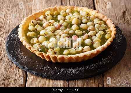 Summer berry tart with gooseberries close-up on a slate plate on a table. horizontal - Stock Photo