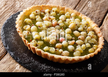 Homemade pie with summer gooseberries and  jam closeup in a board on a table. Horizontal - Stock Photo