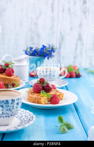 Small pies with berries, strawberries and cherries. Delicious sweet breakfast and fragrant coffee, on a blue wooden background. Flat lay, Copy space, - Stock Photo