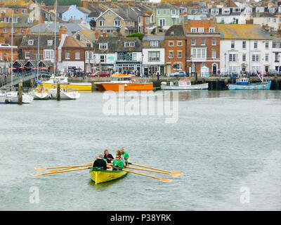 Weymouth, UK. 17th June 2018. A mixed gig-racing crew train in chilly Weymouth harbour on an overcast day in Dorset Credit: stuart fretwell/Alamy Live News - Stock Photo