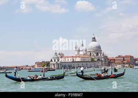 Gondolas  with Asian tourists in front of Punta della Dogana and Basilica di Santa Maria della Salute, Grand Canal, Venice,  Veneto, Italy. Busy biat  - Stock Photo