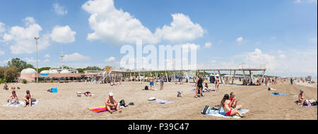 Panorama of Blue Moon Beach, Lido di Venezia, Venice, Veneto, Italy in late spring with the pier and restaurants, people swimming and sunbathing - Stock Photo