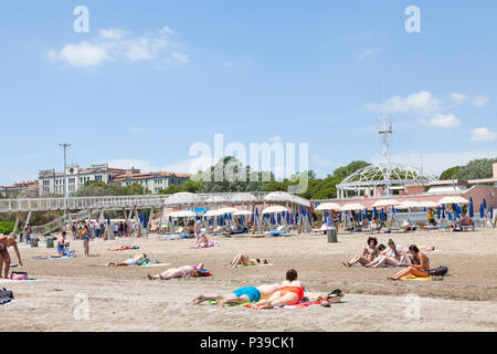 People sunbathing on Blue Moon Beach, Lido di Venezia, Lido Island, Venice, Veneto, Italy, on a sunny late spring day. Pier, restaurants, observation  - Stock Photo