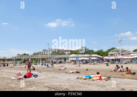 People sunbathing on the sand in front of the pier and restaurant,  Blue Moon Beach, Lido di Venezia, Lido Island, Venice, Italy in late spring - Stock Photo