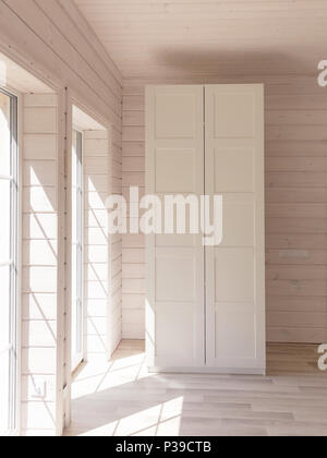Scandinavian style apartments. Light bedroom interior in a organic wooden house of white color. Ikea furniture, wardrobe. Wooden floor, walls, wooden ceiling. White cupboard. Panoramic windows - Stock Photo