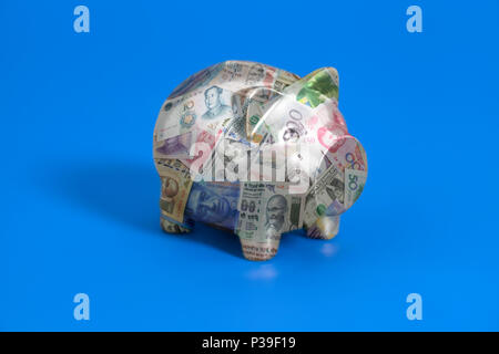 Piggy bank with International currencies banknotes