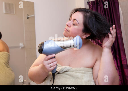 A short haired curvy latina woman closes her eyes and happily goes through her hair routine. - Stock Photo