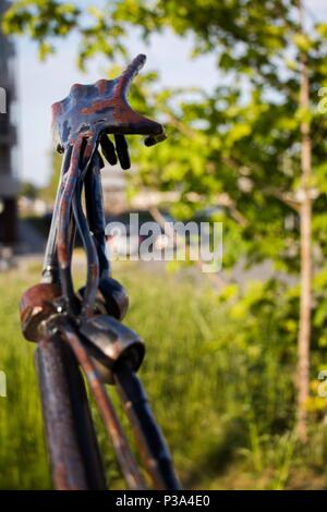 A hand made of iron points to the sky and to a green tree. The hand is slightly covered in rust. Pointing finger indicates directions. - Stock Photo