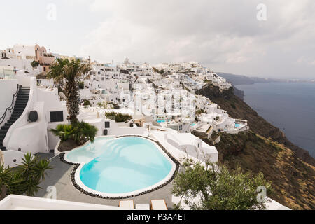 SANTORINI, GREECE - MAY 2018: View over Aegean sea, Firostefani village and volcano caldera with luxury hotel and infinity swimming pool on the foregr - Stock Photo