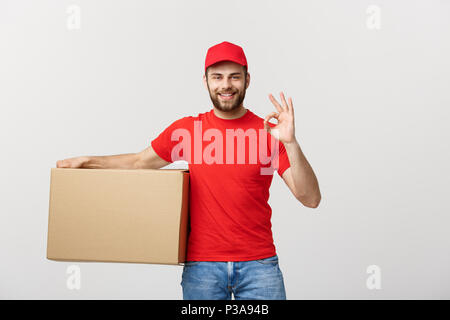 Cheerful young delivery man in red cap standing with parcel post box isolated over white background showing okay gesture. - Stock Photo