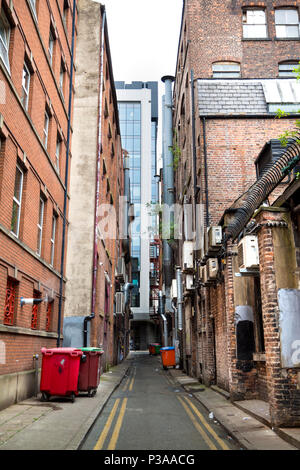 Narrow industrial back alley with pipes and bins, red brick buildings, in Manchester, UK - Stock Photo