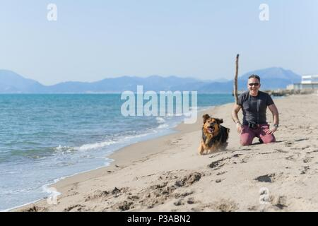 Young caucasian man playing with dog on beach. Man and dog having fun on seaside - Stock Photo