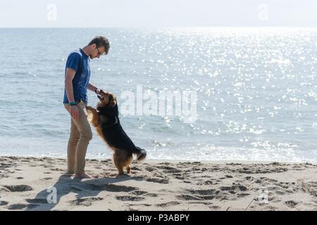 Young caucasian boy playing with dog on beach. Man and dog having fun on seaside - Stock Photo