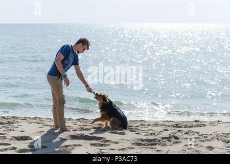 Young caucasian male playing with dog on beach. Man and dog having fun on seaside - Stock Photo
