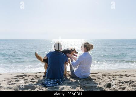 Mom with her son and their dog sitting on the beach watching the sunset - Stock Photo