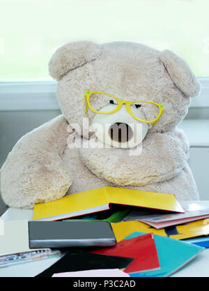 Bear with big glasses reads a stack of colorful books. reading is power! - Stock Photo