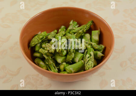 Freshly rinsed chopped raw asparagus in orange bowl on tablecloth - Stock Photo