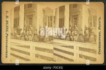 202 Multi-generation male and female family members, wearing suits and dark dresses, pose before white-columned porch and trellis of multi-story clapboard house; white board fence in foreground, by L. R. Bliss - Stock Photo