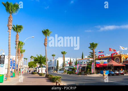 Ayia Napa, Cyprus - June 11, 2018: Agia Napa town on south coast of Cyprus island, street view at summer day. Tourists walk on street - Stock Photo