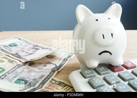 Money worries concept. Unhappy piggy and few banknotes with calculator. Problems with money. - Stock Photo