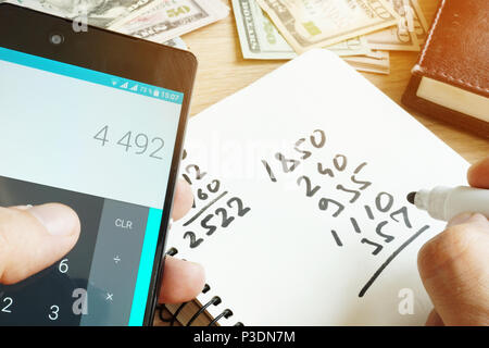 Man with smartphone calculating numbers for home finances. - Stock Photo