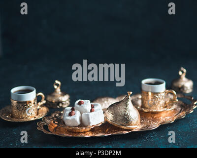 Turkish coffee with delight and traditional copper serving set on dark background. Assorted traditional turkish dilight or lokum and turkish coffee in metal traditional cups.Copy space.Selective focus - Stock Photo