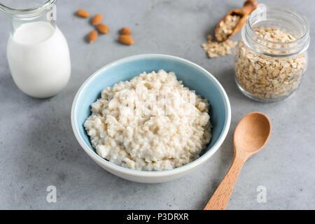 Steel cut oats, oatmeal porridge in bowl. Healthy breakfast on grey concrete table background - Stock Photo