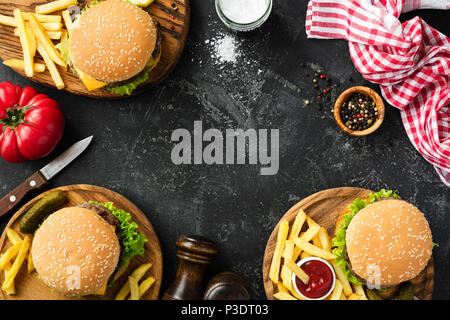 Burgers and french fries on dark stone background, top view with copy space. Homemade hamburgers and fries. Fast food or BBQ concept - Stock Photo