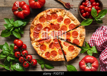Pepperoni pizza, tomatoes and basil. Tasty pepperoni pizza on rustic wooden background. Overhead view of italian pizza - Stock Photo