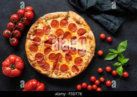Hot pepperoni pizza on black stone background. Sliced tasty pizza with salami, cheese and tomatoes on dark table, top view - Stock Photo
