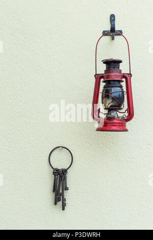 Old hurricane lamp and keys hanging on a textured wall. - Stock Photo