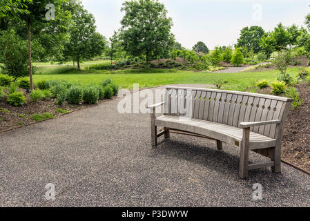 Wooden bench seat in the winter garden at RHS Hyde Hall Essex. - Stock Photo