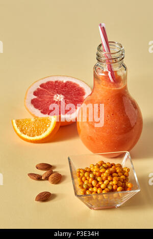 Orange citrus drink with sea buckthorn and almonds in a glass on an orange paper background - Stock Photo