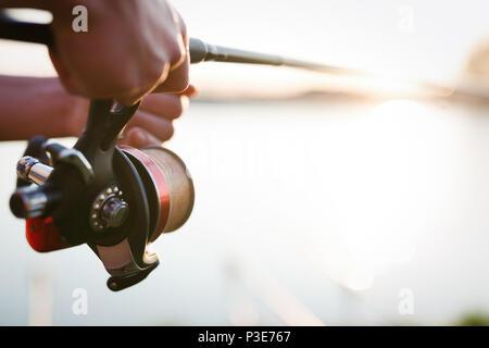Fishing gear - fishing spinning, fishing line and sports equipment - Stock Photo