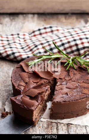 Baked  belgian chocolate cheesecake with chocolate ganache on wooden table - Stock Photo