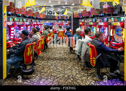 Players in a pachinko hall, Tokyo, Japan - Stock Photo