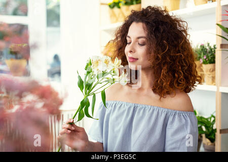 Nice young woman smelling the flower - Stock Photo