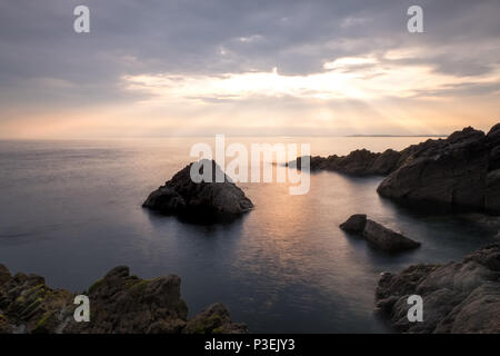 Sun breaking through clouds over the sea on the west coast of Anglesey, near Rhosneigr, Wales,UK - Stock Photo