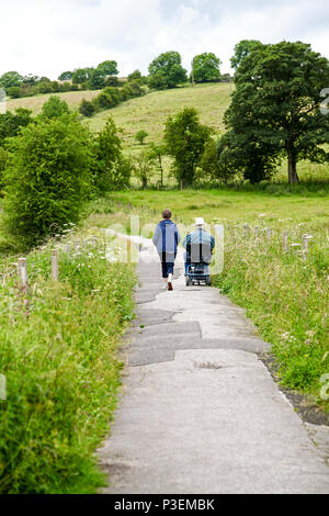 A woman and a man in wheelchair on a path which is on the bed of an old railway, Manifold Valley Staffordshire England UK - Stock Photo
