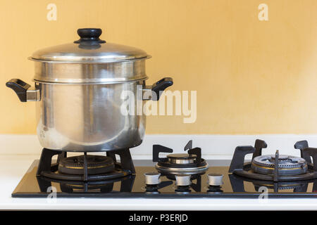 Big hot pot set on gas stove in modern kitchen. - Stock Photo