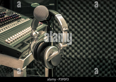 Close up instruments music background concept.Headphones hang  on microphone with sound mixer board in home recording studio.Free space for creative d - Stock Photo