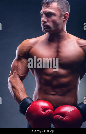 Boxing concept. Handsome boxer in red boxing gloves before a fight against a black background - Stock Photo