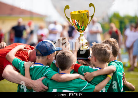 Young Soccer Players Holding Trophy. Boys Celebrating Soccer Football Championship. Winning team of sport tournament for kids children. - Stock Photo