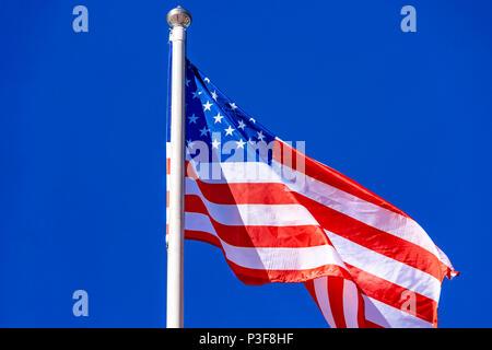 American Flag against blue sky. - Stock Photo