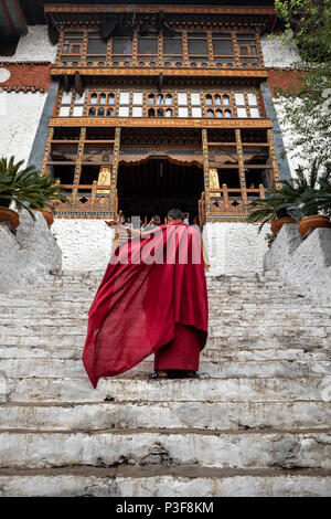 The beauty of Punakha Dzong is incomplete without its monks, drapped in red robe. - Stock Photo