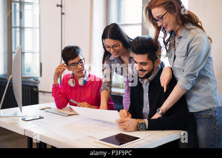 Group of young perspective architects looking at project papers - Stock Photo
