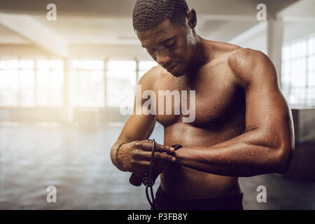 Man setting a timer in his wrist watch standing in the gym. Bare chested muscle athlete holding skipping rope with sweat all over his body after worko - Stock Photo