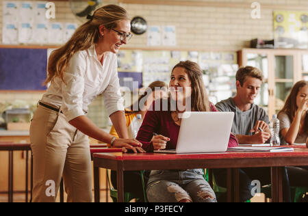 Happy woman high school professor helping students during her class. Group of young people in classroom with helpful teacher. - Stock Photo