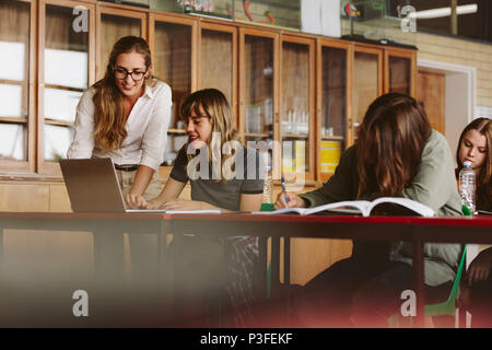 Happy young teacher helping a female student  studying on laptop in classroom. Professor assisting students in lecture. - Stock Photo